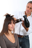 Hairdresser drying woman's hair
