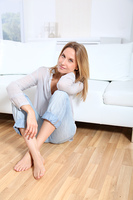Beautiful blond woman sitting on living room floor