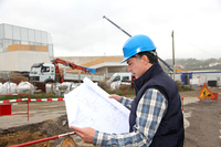 Engineer on construction site with building plan