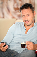 Man at home sitting in couch with cup of coffee