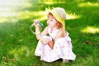 Little beautiful girl blowing soap bubbles