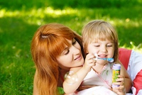 Little beautiful girl blowing soap bubbles with her mom
