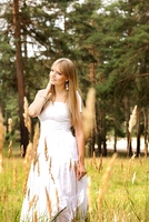 Beautiful young blond woman in white dress at the meadow