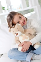 Sick little girl hugging sick teddy bear