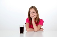Young girl looking at glass of soft drink