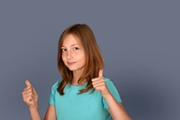 Portrait of young girl with thumbs up