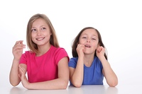 Cute little girls laughing on white background