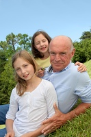 Grandfather with grandkids sitting in park