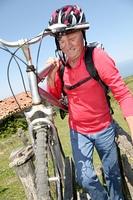 Senior man carrying mountain bike