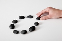 Human hand arranging line of pebbles in circle