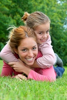 Little girl and mother laying on grass in park