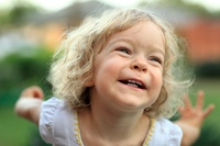 Smiling kid in summer park. Shallow depth of field
