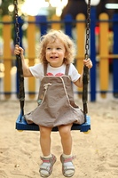 Child on swing in summer park