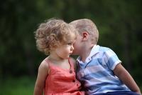 Little boy whispers to lovely girl on ear