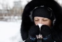 woman blowing nose and sneezing,  winter cold concept with real people
