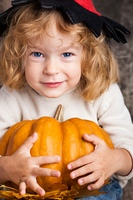 Happy smiling child in hat of witch holding a big orange pumpkin. Halloween concept