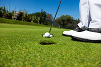 Golfer on the putting green, preparing to put
