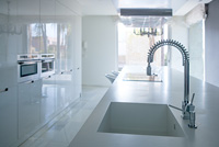 Modern white kitchen perspective with integrated bench sink and spring faucet