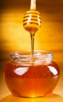 Honey pouring into bowl on wooden table