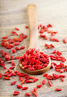 spoon of dried goji berries on wooden table
