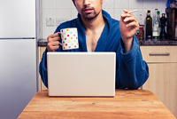Man in bathrobe smoking and drinking while looking at laptop