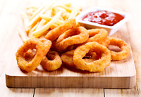 onion rings and fried potato with ketchup on wooden board