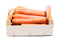 fresh carrots in wooden box on white background
