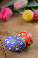 Easter eggs and flowers on wooden table