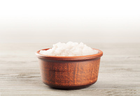 Aromatic bath salt in a clay cup on a wooden surface