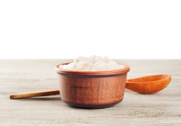 Aromatic bath salt in a clay cup and wooden spoon