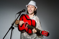 Man with guitar singing with microphone