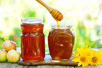Honey pouring into glass jar on wooden table