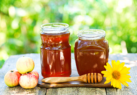 jars of honey on wooden table in the garden