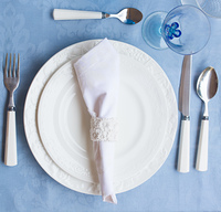 Tableware - set of plates, cups and utencils on blue tablecloth, top view
