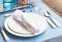 Tableware - set of white plates, cups and utencils on blue tablecloth