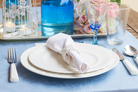 Tableware - set of white plates, glasses and utencils on blue tablecloth
