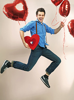 Laughing and jumping guy with valentine's balloons