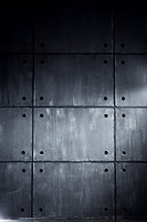 Gray concrete wall with big blocks in contrast dark colors