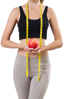 Woman with apple doing exercises on white
