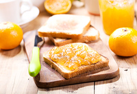 toast with orange mandarin marmalade with fresh fruits on wooden table