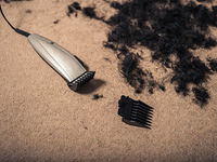 Some hair clippers on the floor with piles of hair around them