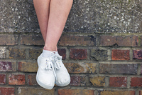 The legs of a young woman as she is sitting on a brick wall and is relaxing