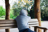 A young person wearing a hooded top is sitting in a shelter in the park