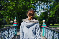 A young woman is crossing a bridge in a park
