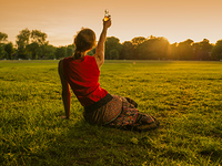 A young woman is drinking in a park and is lifting her bottle saluting the sunset
