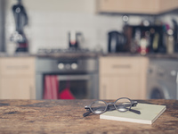 A pair of glasses and a book on a table in a kitchen.