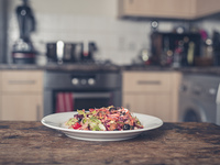 A plate with salad on a table in a kitchen