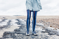 The legs of a young woman as she is standing on the beach with her skirt blowing in the wind