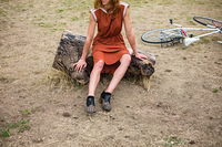 A young woman with bruises on her leg is sitting on a log outside, there is a bicycle in the background