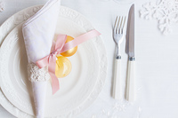 Tableware set. Plates and knofe with fork on white tablecloth with christmas decorations